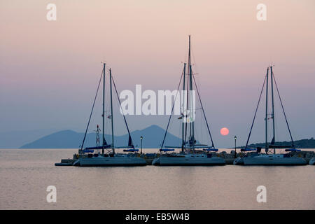 Frikes, Ithaca, Ionian Islands, Greece. View across the harbour at sunrise, the distant island of Atokos visible. - Stock Photo