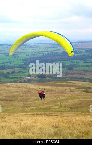 Tandem Paraglider coming into land. West Fell Lake District National Park Cumbria England UK. - Stock Photo