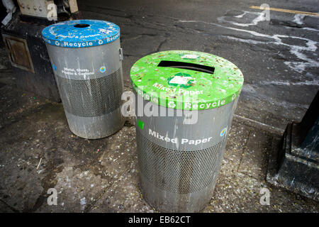 Labeled recycling bins, covered with pigeon droppings, are seen Jackson Heights in Queens in New York - Stock Photo