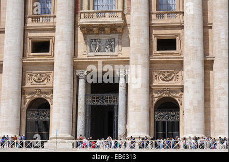 Tourists queuing outside the entrance of St Peter basilica in Vatican City in Rome, Italy. - Stock Photo