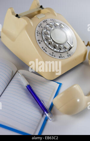 Old fashioned rotary dial telephone with notepad and pen. - Stock Photo