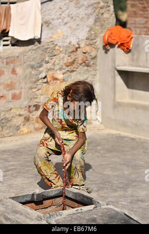 Young Indian girl lifting a water pot from a rain water tank India - Stock Photo