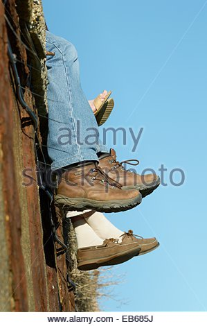Close-up of people sitting on the quayside, with their legs hanging over the edge, at Folkestone, Kent - Stock Photo