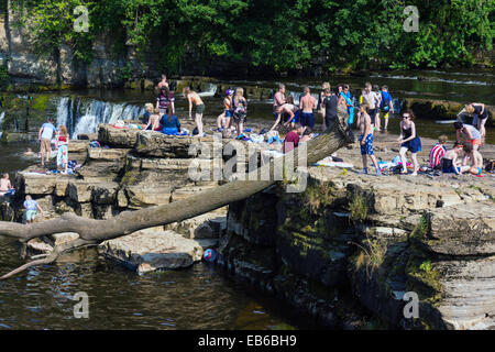 Crowds of young people playing in water, summer on the River Swale, Richmond, North Yorkshire, England - Stock Photo