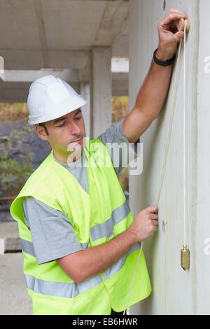 Worker with protective equipment PPE Checking and aligning vertical sections in concrete walls housing construction - Stock Photo