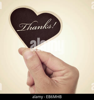 picture of a man hand holding a heart-shaped blackboard with the word thanks written in it, with a retro effect - Stock Photo