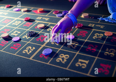 People laying placing bets playing at roulette gambling in a 'casino' at a wedding reception, UK - Stock Photo
