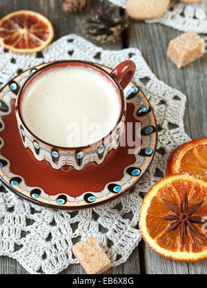 Hot cocoa in a old ceramic cup on a wooden table with pieces of sugar, cinnamon sticks and candied orange slice. - Stock Photo