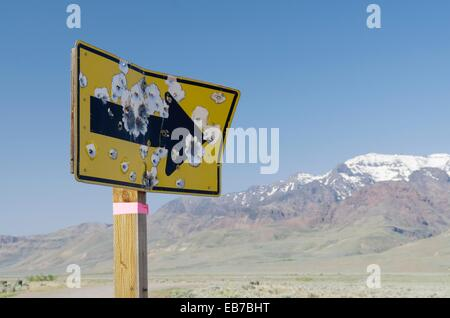 Bullet ridden road sign, Steens Mountain is in the distance, Alvord Desert Oregon - Stock Photo