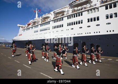 Pipe Band playing on the quay at Greenock near Glasgow on the Firth Clyde Scotland when the cruise liner Queen Elizabeth - Stock Photo