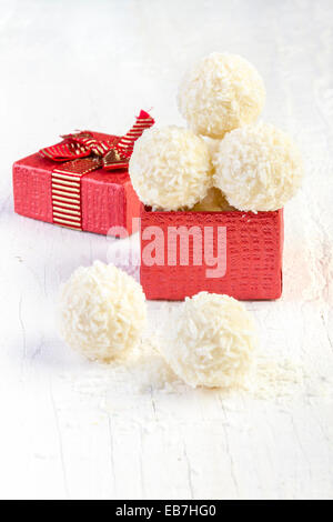 Coconut snowball truffles in the gift box on white background. Arrangement of coconut cookies on wooden elegant - Stock Photo