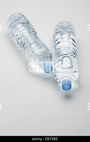 two bottles of mineral water lying without label on white background - Stock Photo