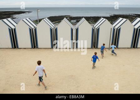 kids playing football behind the bathing huts on the beach Yport near Etretat Cote d´Albatre Pays de Caux Seine - Stock Photo
