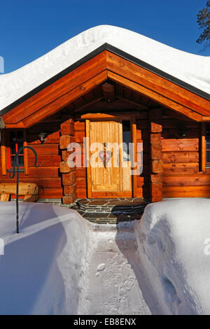Wooden house snow covered in winter - Stock Photo