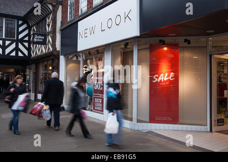 The front of New Look store, passers-by & facade sign. Chester, Cheshire,  New Look store, Eastgate St. on Black - Stock Photo