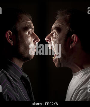In conflict, frustrated, angry at self or even split personality. - Stock Photo