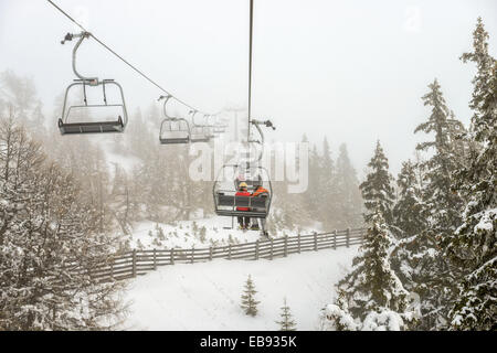 Chairlift with skiers in snowfall at alpine ski resort - Stock Photo