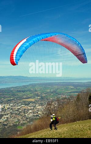 Paraglider taking off from Mont Saleve in France tandem flight panorama Geneva in Switzerland below Mont Saleve - Stock Photo