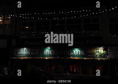 Night view illuminated green name sign above windows, Shenanigans Irish Fun Bar, Central Promenade, Blackpool Illuminations, - Stock Photo