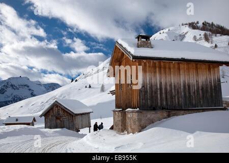 Snow trail alongside wooden barns, near Fuciade hut, San Pellegrino pass, Trentino Alto Adige, Italy, Europe - Stock Photo