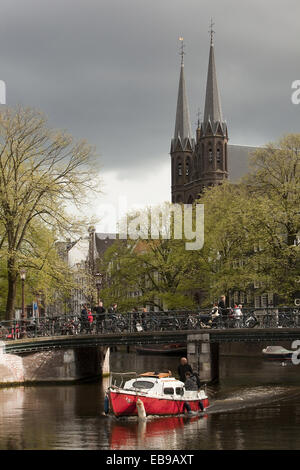 De Krijtberg Roman Catholic church with a boat in the foreground, Single Canal, Amsterdam, Holland, Europe. - Stock Photo
