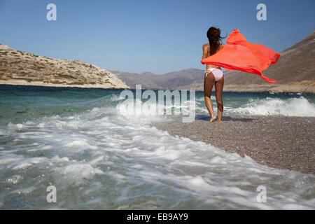 Woman in bikini walking towards the waves at the beach, Amorgos, Cyclades Islands, Greek Islands, Greece, Europe. - Stock Photo