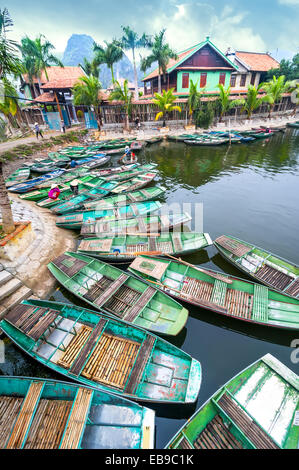 Vietnamese woman with conical hat Amazing morning view with Vietnamese boats at river. Tam Coc, Ninh Binh,. Vietnam - Stock Photo