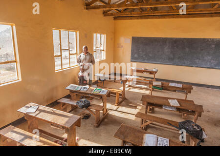 Headmaster and a young student stand by the windows inside a primary school classroom in Northern Tanzania. - Stock Photo