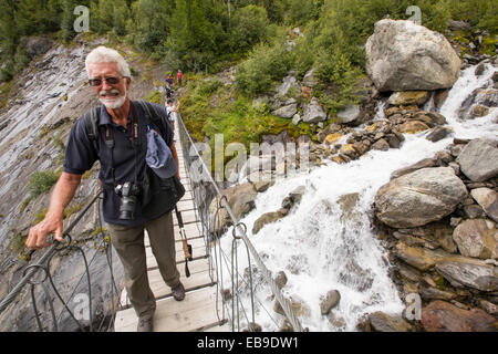 Walkers on the Tour Du Mont Blanc cross a suspension bridge across the meltwater river from the Bionnassay glacier; - Stock Photo
