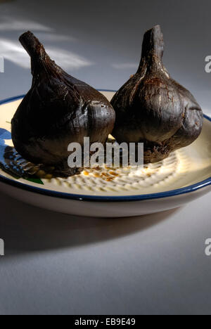 Black garlic bulbs whose unique coffee and chocolate flavor is a result of applying low heat over a period of several weeks