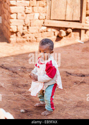 Small child, a dirty toddler with runny nose standing roadside in the street in Antananarivo, or Tana, capital city - Stock Photo