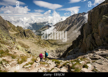 A couple on the Tour du Mont Blanc descend into the Val D' Arpette in the Swiss Alps. - Stock Photo