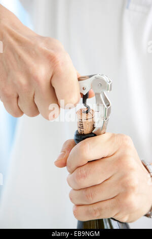 Man's Hands Opening Wine Bottle with Corkscrew - Stock Photo