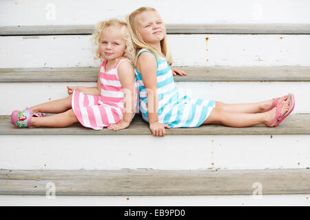 Two Young Girls Sitting Back to Back on Steps - Stock Photo