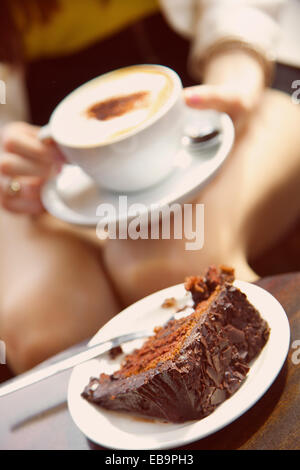 Woman Having Cappuccino and Chocolate Cake, Cropped View - Stock Photo