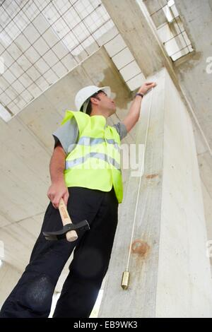 Worker with protective equipment, PPE, Checking and aligning vertical sections in concrete walls, housing construction, - Stock Photo