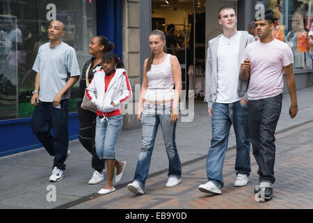 Multiracial group of teenagers walking down a street together, - Stock Photo
