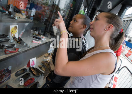 Two teenaged girls looking in a shop window, - Stock Photo
