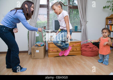 Mother and her daughters playing a skipping game together, - Stock Photo