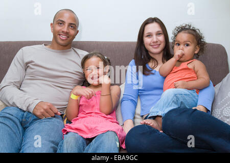 Young family sitting on the sofa together, - Stock Photo