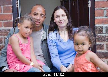 Young family sitting on their doorstep smiling, - Stock Photo
