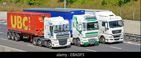 Three hgv articulated trucks and trailers involved in overtaking manoeuvre on four lane motorway - Stock Photo