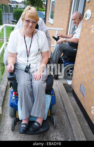 Disabled couple leaving their house down a concrete wheelchair ramp, - Stock Photo