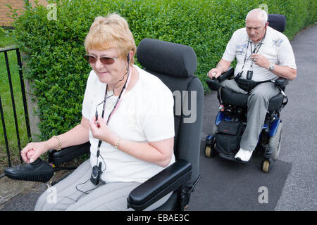 Disabled couple out in the street using mobile phones to communicate with one another, - Stock Photo