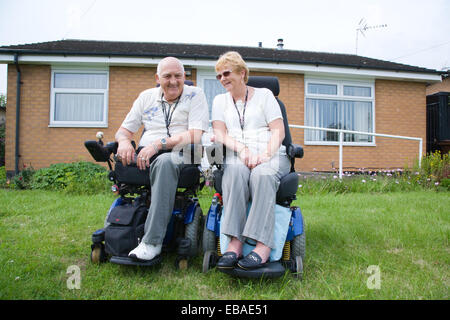 Wheelchair using couple user outside their house; concrete ramp and grab rails in the background, - Stock Photo