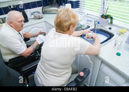Disabled Couple Doing The Washing Up Together In Their Nonadapted Kitchen,    Stock Photo