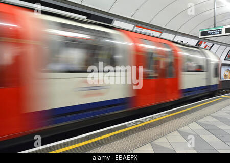 Empty platform on London Underground with motion blur tube train arriving at station - Stock Photo