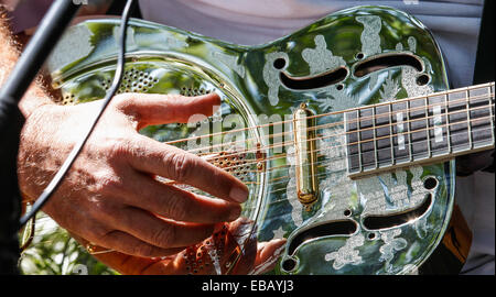 Close-up of hand on strings of a steel guitar at Leighton-Linslade Canal Festival - Stock Photo