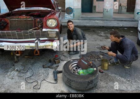 Car mechanics attempt to repair a Cuban classic on the street. Havana, Cuba. - Stock Photo