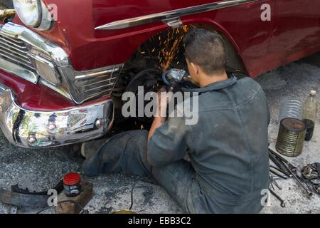 Car mechanic attempts to repair a Cuban classic on the street. Havana, Cuba. - Stock Photo